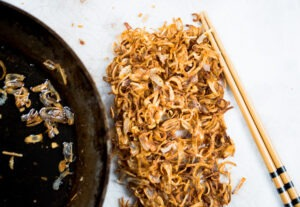 Crispy fried shallots drying on a paper towel